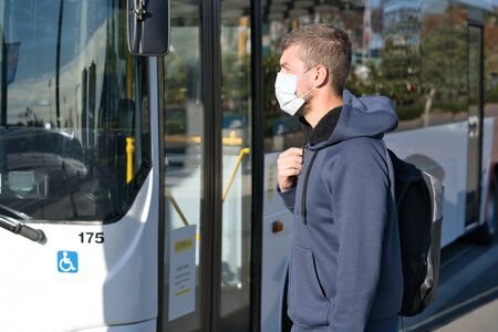 Caucasian man wearing face mask at the bus station. Coronavirus concept