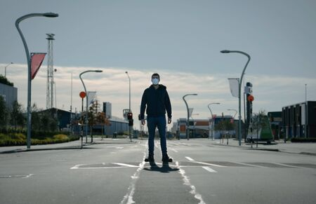 Young man wearing face mask standing in the middle of the road on an empty city centre. Coronavirus concept Foto de archivo