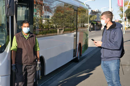 Caucasian citizen and indian bus driver wearing face mask at the bus stop. Coronavirus concept