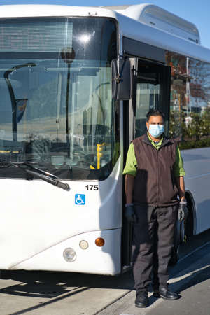 Indian bus driver wearing face mask and gloves against Covid-19 pandemic virus. Vertical photography