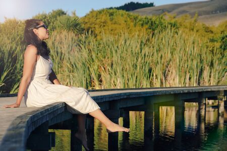 Woman sitting on a wooden walkway enjoying sunlight and admiring the landscape. Inspirational concept