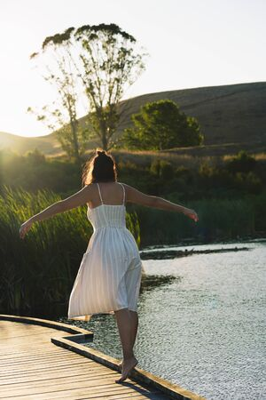 Young woman balancing out on a wooden walkway surrounded by water. Inspirational concept. Vertical photography Foto de archivo