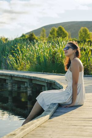 Young woman enjoying the landscape sitting on a wooden walkway. Inspirational concept. Vertical photography Foto de archivo