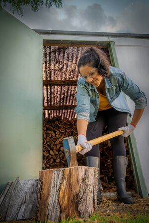 Hispanic woman chopping wood with an ax at home. She is wearing gum boots, protective glasses and gloves. Vertical photography