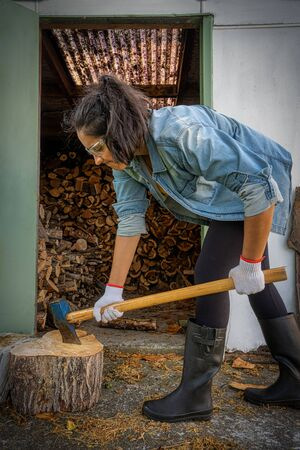 Young brunette woman chopping wood with an ax at home. She is wearing gum boots, protective glasses and gloves. Vertical photography