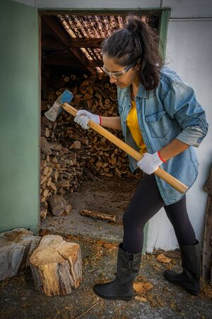 Hispanic young woman chopping wood with an ax at home. She is wearing gum boots, protective glasses and gloves. Vertical photography