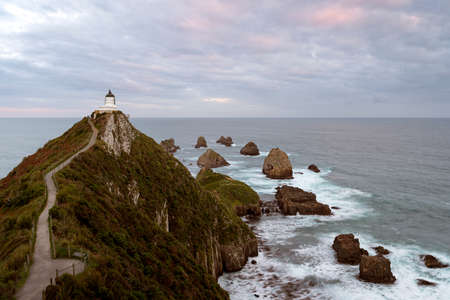 Nugget point and lighthouse above the cliffs in the Pacific Ocean. New Zealand, South Island. Stock fotó