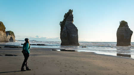 Woman walking in Three Sisters rock formations, coast of New Plymouth, New Zealand. You can see Mount Taranaki behind.