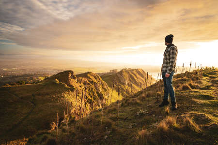 Young man looking at the horizon at the top of a mountain. Hawke's Bay, New Zealand
