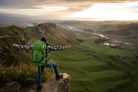Backpacker man opening his arms while standing at the top of a mountain. Traveler concept Standard-Bild
