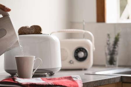 Breakfast time with electric kettle, toaster and an old vintage radio. White background