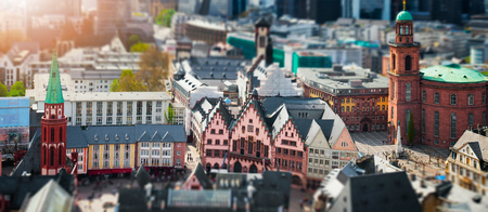 Frankfurt, Germany aerial view panorama with sunlight. City center with city hall and church. Tilt shift blur effect. Abstract cityscape with old architeture buildings.