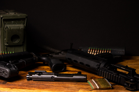 AR-15 broken down in dark setting with ammunition