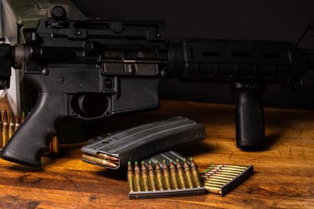 Ciemna oprawa z AR-15 z amunicją 5,56 i magazynkami