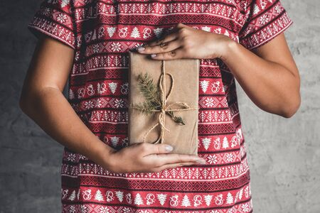 Female wearing a red with red christmas dress has a christmas gift in her hands Stock Photo