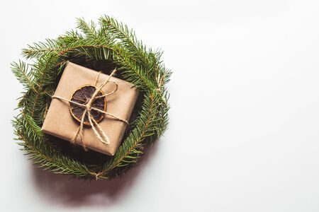 Gift in craft paper in a wreath of Christmas trees. Christmas mood, New Year, On white background Stock Photo