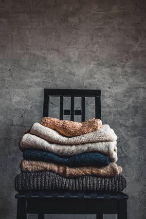 une pile de pulls tricotés chauds et confortables, sur une chaise près du mur gris. automne, concept d'hiver.