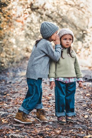 Little girl whispers a secret to her sistersitting against the background of nature. Sisters friendship