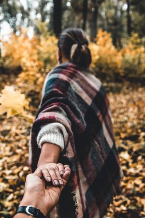 A young girl holds hands and leads a guy forward into the autumn to adventure, concept follow me