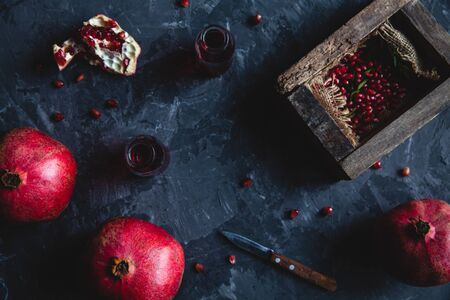 Red pomegranate juice in a glass, ripe and cut pomegranate and a sprig of mint on a gray concrete background. Vitamin, antioxidant and health food concept. Flat lay.Top view. Banco de Imagens