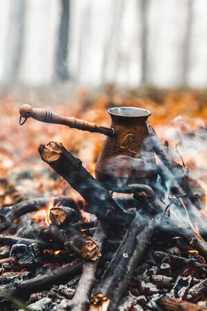 Making coffee at the stake. Make coffee or tea on the fire of nature. Burned fire. A place for fire. Ashes and coal. Banque d'images - 138235172