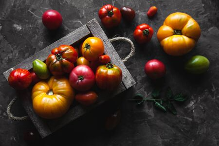 Fresh tomatoes in an old box. On wooden background.