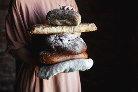 Fresh bread in the hands of a baker. Food, baking Stock fotó