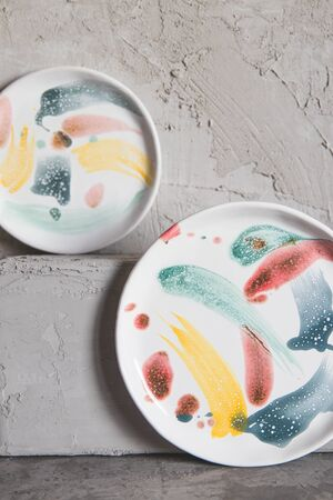 Ceramic plates painted in paints, on a gray background. Stock fotó