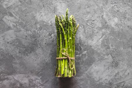 Fresh bunch of asparagus with smooth daylight on grey stone backgroundtop view and free space for text