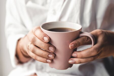 Woman in a white t-shirt holds morning coffee in a pink ceramic cup. Manicure. Front view