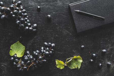blue grapes on a dark background with a black notebook and a cup of coffee. Stock fotó