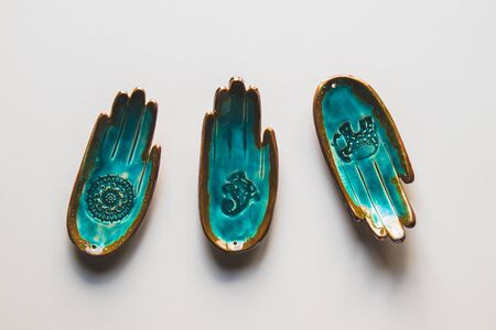 unusual turquoise plate in the shape of a hand on a white background. Ethnic theme Stock fotó