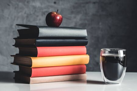 A cup of coffee near of stack of books on grey background Stock fotó