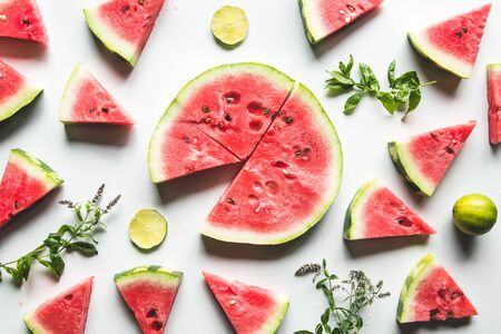Red slices of ripe watermelon with mint leaves and lime slices on a white background. Top view, flat lay