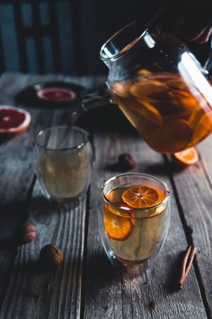 Citrus tea in a transparent teapot and a glass, healthy drink on a wooden background.