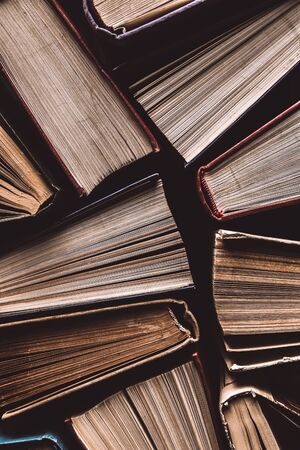 Old and used hardback books or text books seen from above. Books and reading are essential for self improvement, gaining knowledge and success in our careers, business and personal lives Banque d'images