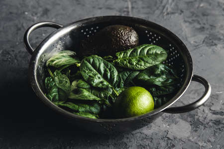 Fresh mini spinach in a colander on the old concrete table. Healthy food, eco product. Vegan