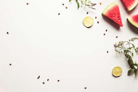 Red slices of ripe watermelon with mint leaves and lime slices on a white background.