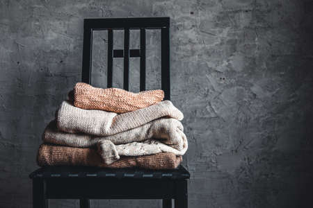 a stack of knitted warm cozy sweaters , on a chair by the gray wall. autumn, winter concept.