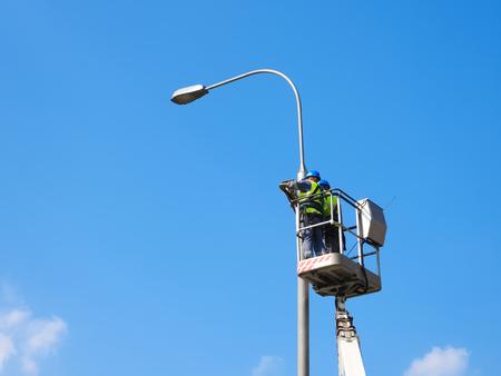 Workers repair the street lighting support Stockfoto