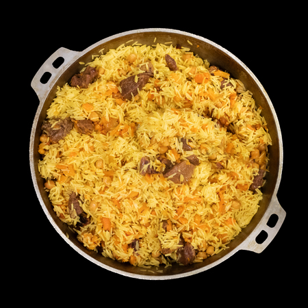 Top view of pilaf in a large pan isolated on black. Eastern cuisine
