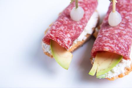 Bruschetta crostini with salami, avocado and ricotta cheese. Italian cuisine