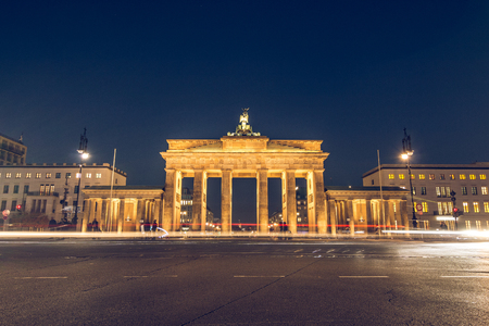 Brandenburg gate at night with rear view. Lanterns illuminate the street. Light from passing cars is visible. the monument is illuminated by light.