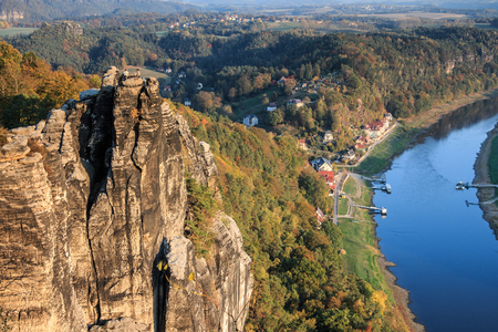 Rock formation in the Elbe Sandstone Mountains in the Saxon Switzerland National Park. Sunshine in autumn with woods and houses in the background