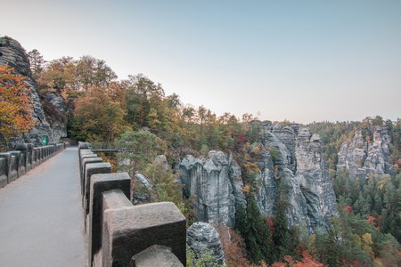 Panoramic view from the Bastei bridge on the Elbe sandstone mountains in autumn mood with trees and rocks formation in the national park Saxon Switzerland