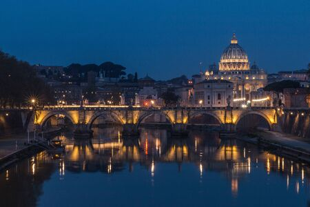 Tiber and St Peters Basilica with Aurelius Bridge or Ponte Sisto Bridge at the blue hour with artificial lighting and reflections. Stone bridge at night over Tiber River in the historic center of Rome