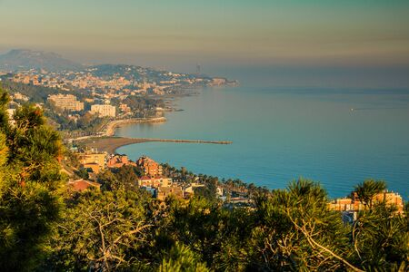 View of the Spanish Mediterranean coast in Nerja from the Balcon de Europa. Sunny autumn day with a view of a village and hills on the horizon. Blue sky with clouds and palm trees in the foreground 版權商用圖片