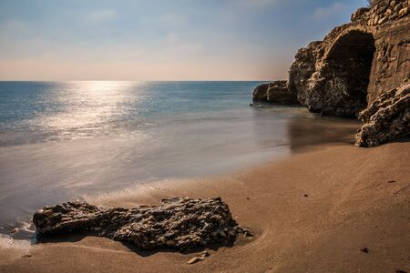 Beach on the Mediterranean coast in Nerja. Sandy beach on the Spanish coast of Costa del Sol. Stone in the sandy beach with rocks and stone arch on sunny day with blue sky and clouds