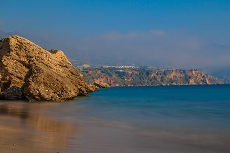 Coastal section on the Spanish Mediterranean coast in Andalusia. Costa del Sol with rocks and blue water in sunshine. Blue sky and cityscape in the background