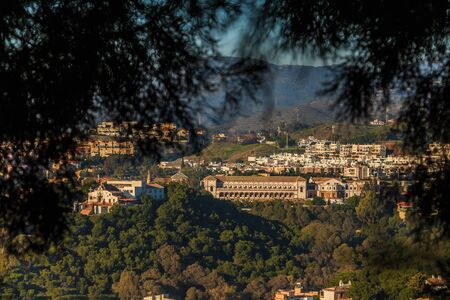 View from the hill to the district of Malaga with the university. Hills with forest and trees on a sunny day. University in the village with buildings